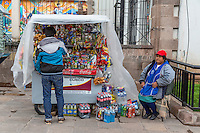 Peru, Cusco.  Young Man Stopping at a Streetside Snack Stand.