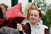 Pictured: A young woman holds a balloon in memory of Bradley John outside St John Lloyd School, in Llanelli, Carmarthenshire, UK. Thursday 12 September 2019<br /> Re: The family of a bullied pupil were joined by friends and held a minute's silence, a year after he hanged himself in school toilets.<br /> His heartbroken father Byron John claims his son Bradley, 14, would still be alive if the school had acted to stop the bullies.<br /> Bradley's 13-year-old sister Danielle found him dead in the toilet block at, an hour after going missing at St John Lloyd Roman Catholic School in Llanelli, South Wales, UK.