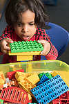 Education Childcare 3 year olds boy building with colored plastic Duplo bricks