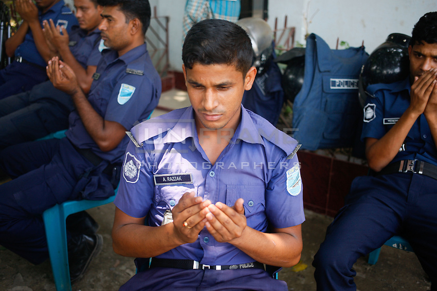 A police man prays at Adhad Chandra High School.