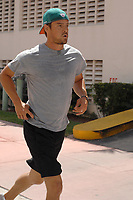 MIAMI BEACH, FL - SEPTEMBER 12: Actor Josh Duhamel goes for a jog while wearing and showing support for his wife's team the Miami Dolphins (she's an owner). The Dolphins lost in their usual embarrassing fashion as quarterback Tom Brady torched the Dolphins for 517 yards, 4 TDs in Patriots win over the Fins.  The Dolphins have not won a season opener in years. Perhaps Josh was to embarrassed to walk the orange carpet and be associated with the losing Dolphins at the game yesterday.  On September 13, 2011 in Miami, Florida<br /> <br /> People:  Josh Duhamel