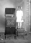 REACHING THE PHONOGRAPH. A little girl stands proudly next to a brand-new Edison C-150 Sheraton design phonograph. The phonograph was introduced in June 1915 and manufactured until 1918. It was a very popular model and became Edison's second-best seller in 1917.<br /> <br /> Photographs taken on black and white glass negatives by African American photographer(s) John Johnson and Earl McWilliams from 1910 to 1925 in Lincoln, Nebraska. Douglas Keister has 280 5x7 glass negatives taken by these photographers. Larger scans available on request.