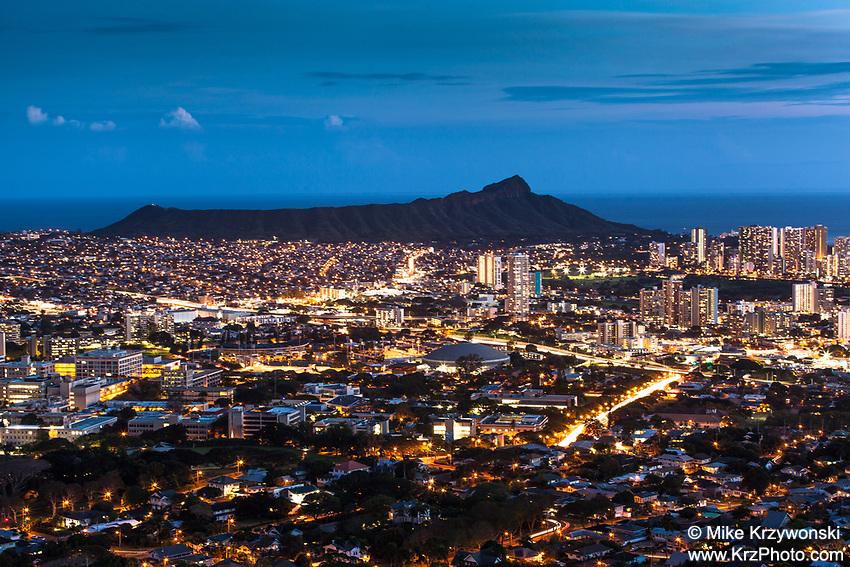 Aerial view of Diamond Head  behind lit buildings at night in Honolulu as seen from Tantalus Lookout