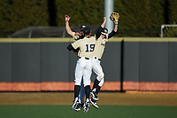 Wake Forest Demon Deacons outfielders Christian Long (19), D.J. Poteet (4), and Nick DiPonzio (7) celebrate following their win over the Gardner-Webb Runnin' Bulldogs at David F. Couch Ballpark on February 18, 2018 in  Winston-Salem, North Carolina.  The Demon Deacons defeated the Runnin' Bulldogs 8-4 in game one of a double-header.  (Brian Westerholt/Four Seam Images)