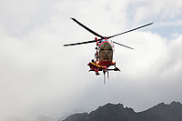 "Switzerland. Canton Ticino. Blenio valley. A Rega Agusta AW109 SP Grand ""Da Vinci"" helicopter lon a rescue operation. By using a rescue hoist, a helicopter can rescue persons from hard-to-reach areas in the Alps. The emergency physician, Doctor Damiano Salmina, takes care of a badly injured man lying in a rescue bag. The patient is a worker from the Rotex company who was injured during a logging operation. All Rega helicopters carry a crew of three: a pilot, an emergency physician, and a paramedic who is also trained to assist the pilot for radio communication, navigation, terrain/object avoidance, and winch operations. The name Rega was created by combining letters from the name ""Swiss Air Rescue Guard"" as it was written in German (Schweizerische Rettungsflugwacht), French (Garde Aérienne Suisse de Sauvetage), and Italian (Guardia Aerea Svizzera di Soccorso). Rega is a private, non-profit air rescue service that provides emergency medical assistance in Switzerland. Rega mainly assists with mountain rescues, though it will also operate in other terrains when needed, most notably during life-threatening emergencies. As a non-profit foundation, Rega does not receive financial assistance from any government. People in distress can call for a helicopter rescue directly (phone number 1414). The AgustaWestland AW109 is a lightweight, twin-engine, helicopter built by the Italian manufacturer Leonardo S.p.A. (formerly AgustaWestland, Leonardo-Finmeccanica and Finmeccanica). Leonardo S.p.A is an Italian global high-tech company and one of the key players in aerospace. In close collaboration with the manufacturer, the Da Vinci has been specially designed to cater for Rega's particular requirements as regards carrying out operations in the mountains. It optimally fulfills the high demands made of it in terms of flying characteristics, emergency medical equipment and maintenance. Safety, performance and space have been increased, and maintenance and noise emissions reduced. 19."