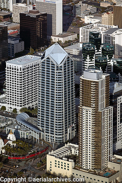 Aerial photograph of One America Plaza, 600 West Broadway, designed by Murphy/Jahn Architects and KMA Architecture. The office tower base features a glass enclosed trolley station. Adjacent towers include Sempra Energy building, Commonwealth Financial, San Diego, California