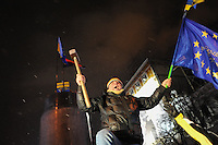 An outraged demonstrator holds a European flag and a sledge-hammer in sign of protest after the fall of the statue of Vladimir Lenin