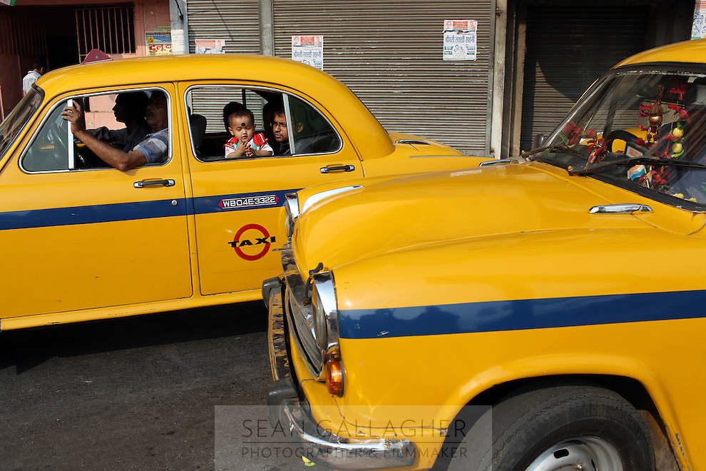 """A young child looks out from one of Kolkata's iconic """"Ambassador"""" taxis. Traffic is an increasing problem which is choking the city. India. November, 2013"""