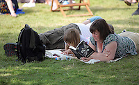 Pictured: A woman and a girl are reading books on the festival green Monday 30 May 2016<br />Re: Hay Festival, Hay on Wye, Wales, UK