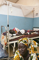 Senegal. Thies region. Mekhe. Hospital ( District sanitaire). Cheick Ibra Diouf is a young man sick from malaria and is  lying in bed. He is on an intravenous drip. His sister, covering her hair with a colorful loincloth, seats on the ground near the bed. 04.12.09 © 2009 Didier Ruef