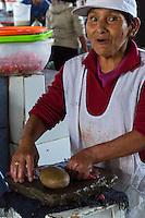 Peru, Cusco.  San Pedro Market.  Woman Pounding Meat with a Stone to Tenderize it.