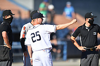 Home plate umpire Adam Clark, Aberdeen IronBirds manager Kyle Moore, Asheville Tourists manager Nate Shaver (25) and umpire Clay Williams go over ground rules before a game on June 15, 2021 at McCormick Field in Asheville, NC. (Tony Farlow/Four Seam Images)