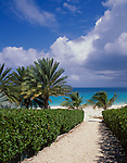 Anguilla, BWI<br /> A hibiscus hedge borders a pathway leading down to a deserted white sand beach and turquoise Caribbean waters of Long Bay