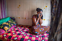 "India; Maharashtra; Mumbai; Bombay. The red light district Falkland Road. A 30- year old sex traffic worker in the brothel. At the age of 14 she married a 28 -year -old, one of her cousins. They had one child who is now 14. After two years her husband got into drinking and left her. She is from Bangalore and left her son with her mother to come to Mysore to be a cook in a hostel. While working there five of the girls went out to watch a movie. Some men invited them for a drink. When she woke up she was in this brothel in Bombay and forced into prostitution. She's now been here ten years. <br /> ""I bought a house for my mother and son, I go back and visit but I have to return here to work to pay for it. I don't know what else to do. My mother thinks I am still working as a cook in the hostel. I'm resigned to the fact that this is my life now.""<br /> She breaks down crying talking about her son."