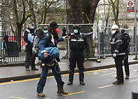A protester is escorted from the area by officials during a protest against the building of the HS2 railway line at Euston Square Gardens on 27th January 2021