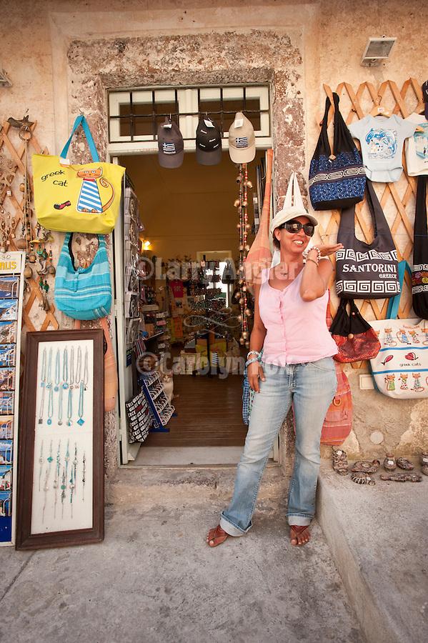 Woman shop keeper at the entrance to her shop, Pyrgos, Santorini, Greece