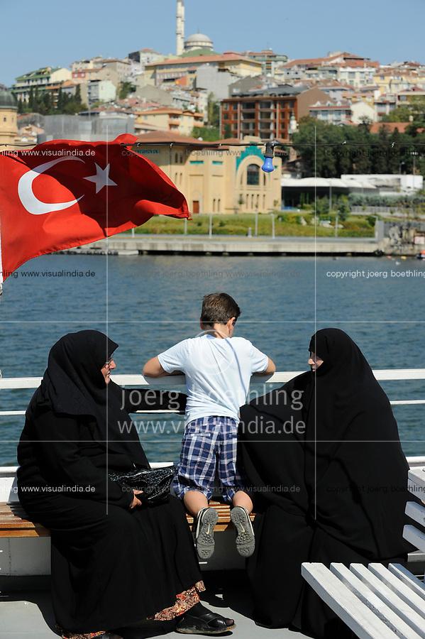 TURKEY Istanbul, Golden Horn, two veiled muslim women with child at ferry boat with turkish national flag / TUERKEI Istanbul, zwei vollverschleierte Frauen mit Kind auf Faehre am Golden Horn