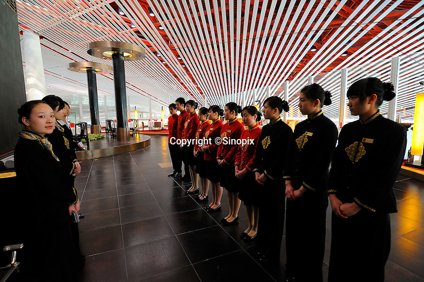 Waiters and waitresses line up at a restaurant to listen to manager's instructions in Terminal 3 Beijing International Airport. Designed by British architect Lord Norman Foster, the new terminal is the world's largest airport building and will help tackle a passenger surge during the Olympics..
