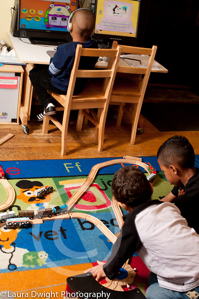 Education Preschool 4 year olds two boys play with train set in foreground boy wearing headphones plays computer educational game