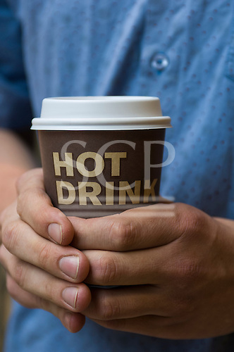 London, England. Hands round a Hot Drink in a takeaway paper/plastic cup.