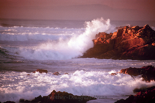 Sun sets on the pacfic coast in Pacific Beach California, as waves pound and spray