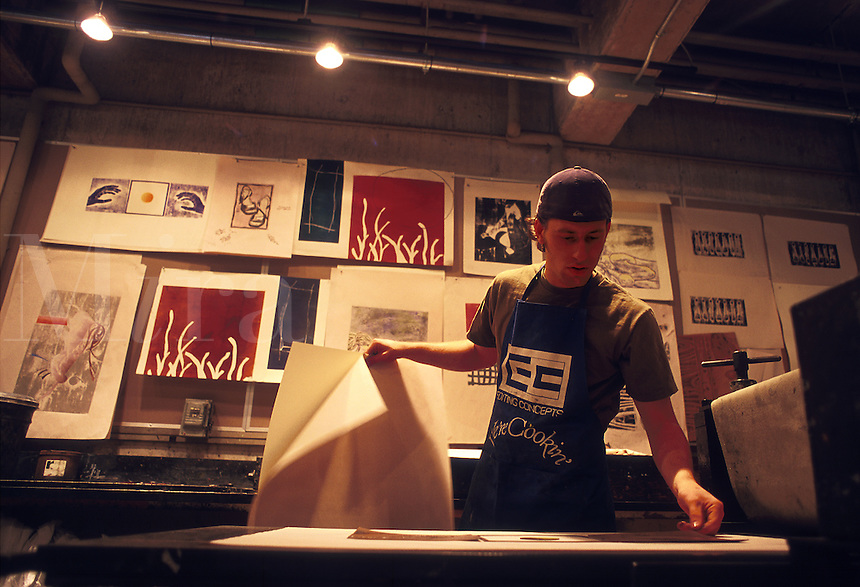 A male college student works in a printmaking studio. Wesleyan University.