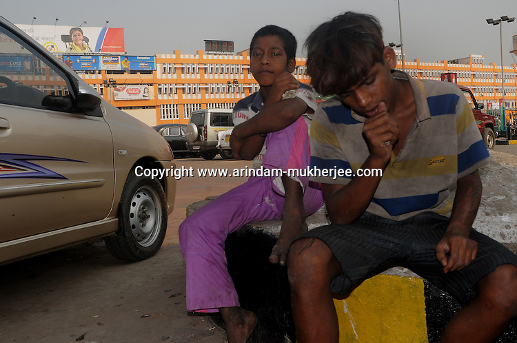Alamgir and his mate Abhijit at the Sealdah railway premises. He is staying here for last 6 years from the time he ran away from his home due to domestic violence and poverty. As per his version his father was a drunkard and used to beat his mother for no reason. His father even could not earn enough money to buy food for their big family. Due to this traumatic situation he ran away from house at the age of seven. Ever since, the Sealdah railway station in Kolkata has been his home. As far as company is concerned, he had not much reason to miss his family. There are around 500 children, from 5 to 16 years, who live in the premises of Kolkata's second largest train terminus. Most of them addicted to Brown Sugar and sniffing industrial adhesive Dendrite. They say they don't feel hungry if they take the drugs. Their presence is conspicuous, even in a place that registers an average footfall of 1.4 million on weekdays. Their activities cover a wide range, from begging, to pulling handcarts, to petty theft, to selling odds and ends on the platform or on trains. The money, earned or ill-gotten as the case may be, is spent in procuring heroin, brown sugar, cocaine, and tubes of Dendrite. Calcutta, West Bengal, India. Arindam Mukherjee