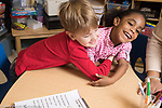 Education Preschool 4 year olds boy spontaneously giving hug to classmate, who is laughing