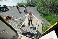 Conductor Bill Haggert puts stairs in place so passengers who have just floated the Placer River can board the train. The Alaska Railroad's Spencer Glacier Whistlestop train gives visitors access to hiking, camping and stunning views.