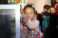 A Tibetan girl in a shop in the town of Zaduo, in the far interior of the Tibetan Plateau, in western China. Relocation communities been created to house nomadic herders moved from the highland grasslands. The nomads have been blamed for contributing to the deterioration of the grasslands, so have been moved, sometimes forcibly, into newly built towns that can be found across the plateau.