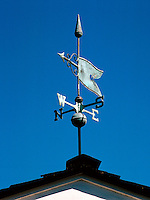 Weathervane with compass direction points on a residential rooftop. Torrance, California.
