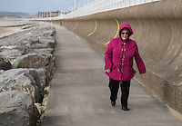 WEATHER PICTURE WALES Thursday 23 February 2017<br /> Walkers brave high winds and whipping sands at Aberavon Beach, Port Talbot, Wales, UK