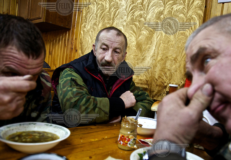 Truck drivers working for the oil and gas prospecting company Siesmorevzedka eat together after work in a camp in the Arctic tundra. /Felix Features