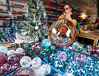 BNPS.co.uk (01202 558833)<br /> Pic:PhilYeomans/BNPS<br /> <br /> Over 10,000 are produced annually.<br /> <br /> I'm forever blowing Baubles...!<br /> <br /> Britain's biggest hand blown Christmas bauble factory is working flat out at this time of year to keep up with demand for the festive favourite.<br /> <br /> 10,000 baubles are blown and individually signed every year at Bath Aqua Glass using raw silica for the blue tinged glass that is then coated with a mixture of copper, iron, manganese or even gold oxide to create colourful and unique designs.<br /> <br /> Evidence of glass making dating back to Roman times have been discovered in the historic Somerset town and boss Annette Dolan keeps the tradition alive with the delicate creations being sent all over the world.