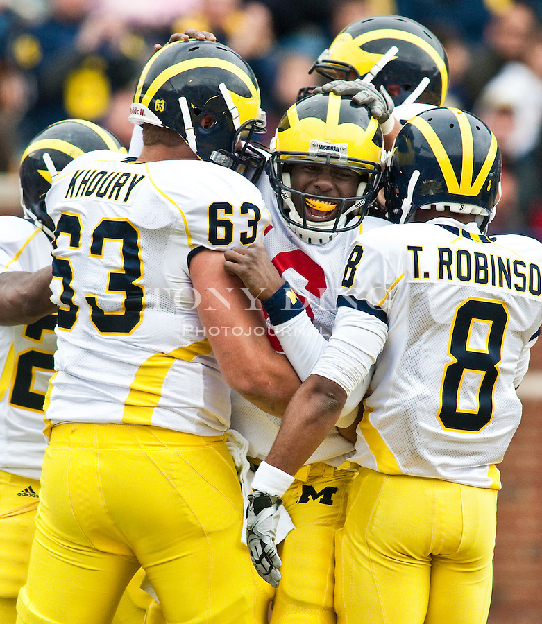 Michigan quarterback Denard Robinson, center, is congratulated by offensive lineman Rocko Khoury (63) and slot receiver Terrence Robinson (8) after scoring a touchdown, during the Wolverines' spring football game, Saturday, April 17, 2010, in Ann Arbor, Mich. (AP Photo/Tony Ding)