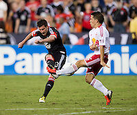 Chris Pontius (13) of D.C. United tries to take a shot with Connor Lade (16) of the New York Red Bulls defending during the game at RFK Stadium in Washington, DC.  D.C. United tied the New York Red Bulls, 2-2.