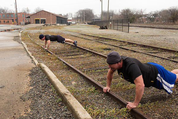 December 22, 2014. Lexington, North Carolina.<br />  Mayor Newell Clark, left, and his cousin Stan Lanier do pushups on the railroad tracks next to the abandoned Lexington Furniture factory.<br />   Newell Clark, the 43 year old mayor of Lexington, NC, leads a group of friends and colleagues on a 4 times a week exercise routine around downtown. The group uses existing infrastructure, such as an abandoned furniture factory, loading docks, stairs, and handrails to get fit and increase awareness of healthy lifestyles in a town more known for BBQ.<br /> Jeremy M. Lange for the Wall Street Journal<br /> Workout_Clark