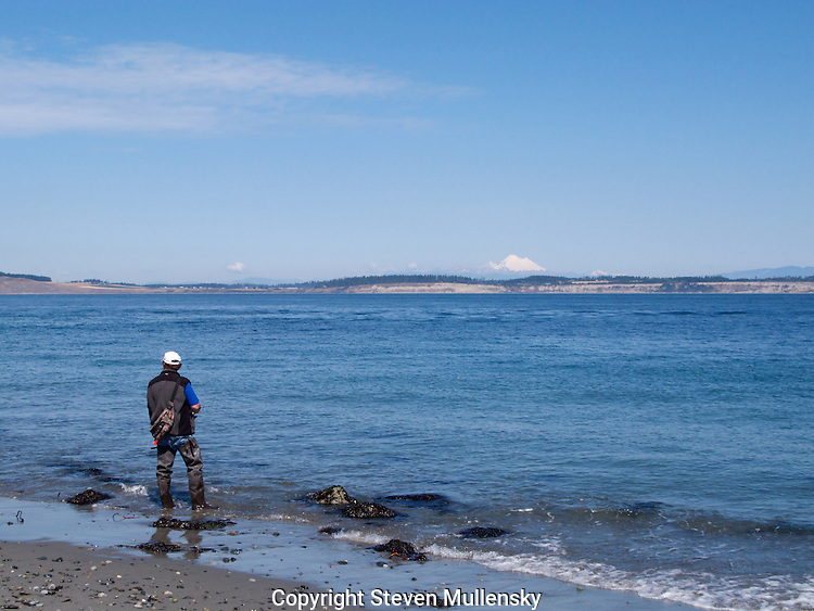 An angler fishes for salmon  along the Strain of Juan de Fuca in the state of Washington. Mount Baker is in the background.