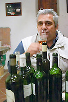 Jean-Louis Poudou with lots of bottles. Domaine La Tour Boisee. In Laure-Minervois. Minervois. Languedoc. Owner winemaker. France. Europe. Bottle.
