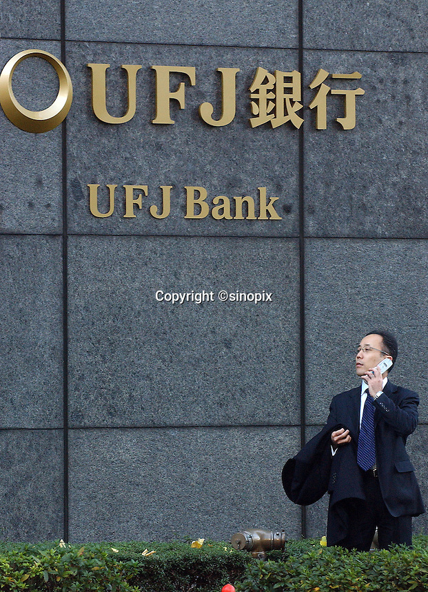 Businessmen pass the UFJ Bank in Tokyo's main business and financial district, Tokyo, Japan..