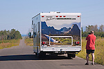 Driver photos CruiseAmerica rental RV in Grand Tetons near Mormon Row, where wildflowers front the view across Antelope Flats to the Teton Range.  Grand Teton National Park, United States, Wyoming.  Mormon Row is a line of historic homesteads along Jackson-Moran Road, Grand Teton National Park.