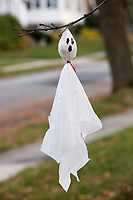 Hand-made ghost decorations hang from a tree on Orchard Street in Belmont, Massachusetts, USA, before Halloween.
