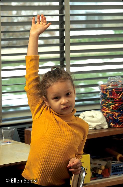 MR / Schenectady, NY.Zoller Public School - Inclusion Class - Grade 1.Girl (6, African-American / Caucasian) raises hand in class..MR: Avi1.© Ellen B. Senisi