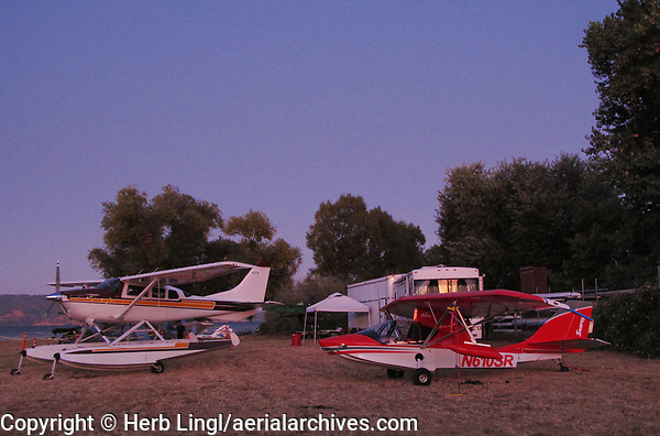 A turbine Cessna CTU206, N247CB on floats and a Progressive Aerodyne SeaRey LSA, N610SR, at  dusk at the Clear Lake Seaplane Splash-In, Lakeport, Lake County, California.  A SeaMax, M-22, N153KC, is parked behind the Cessna 206, only a small portion of that aircraft is visible in this photograph.