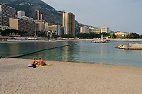 View on the Principality of Monaco, Mediterranean Sea. The photo shows the Larvotto beach with buildings in the background. People resting on the sand and sun tanning. Monaco is the second smallest country in the world after Vatican City. (No MR)