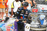 19 June, 2011: Denny Hamlin celebrates with champagne after winning the 43rd Annual Heluva Good! Sour Cream Dips 400 at Michigan International Speedway in Brooklyn, Michigan. (Photo by Jeff Speer :: SpeerPhoto.com)
