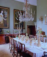 Green damask covers the walls of this dining room and a pair of Jacobean portraits look down on the table which is laid for dinner