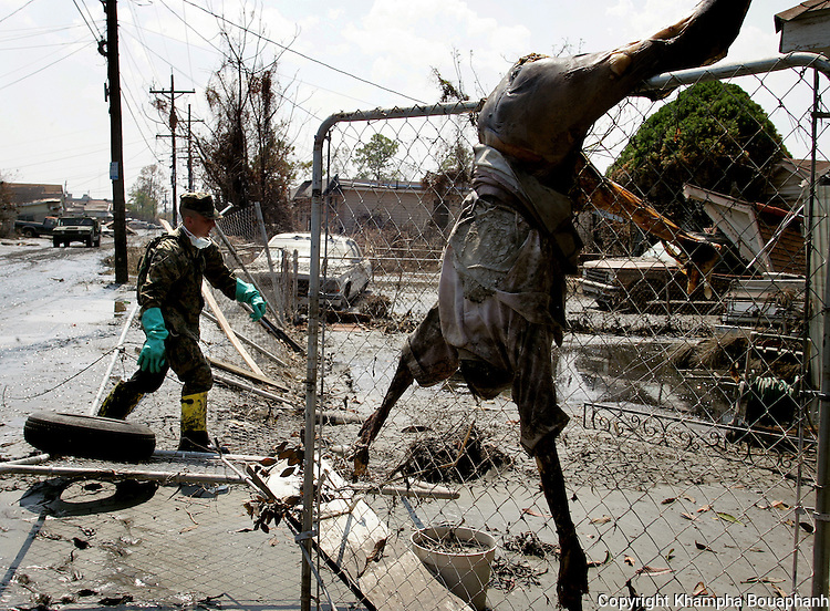 A body dangles on a fence as a Marine conducts a house to house search in the ninth ward of New Orleans on Monday, September 12, 2005.  Hurricane Katrina devasted the city.  (photo by Khampha Bouaphanh)