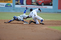 Asheville Tourists second baseman Juan Ciriaco #2 tags out Mark Threlkeld #26 as he slides past the bag during a game against the Lexington Legends at McCormick Field on June 16, 2013 in Asheville, North Carolina. The Tourists won the game 8-7. (Tony Farlow/Four Seam Images)