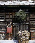 A light covering of snow on an old wooden building with a bunch of mistletoe hanging on the door, a basket of logs standing outside and a small sledge hooked by the doorway.